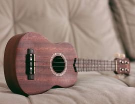 A wooden ukulele on a sofa, waiting to be played.